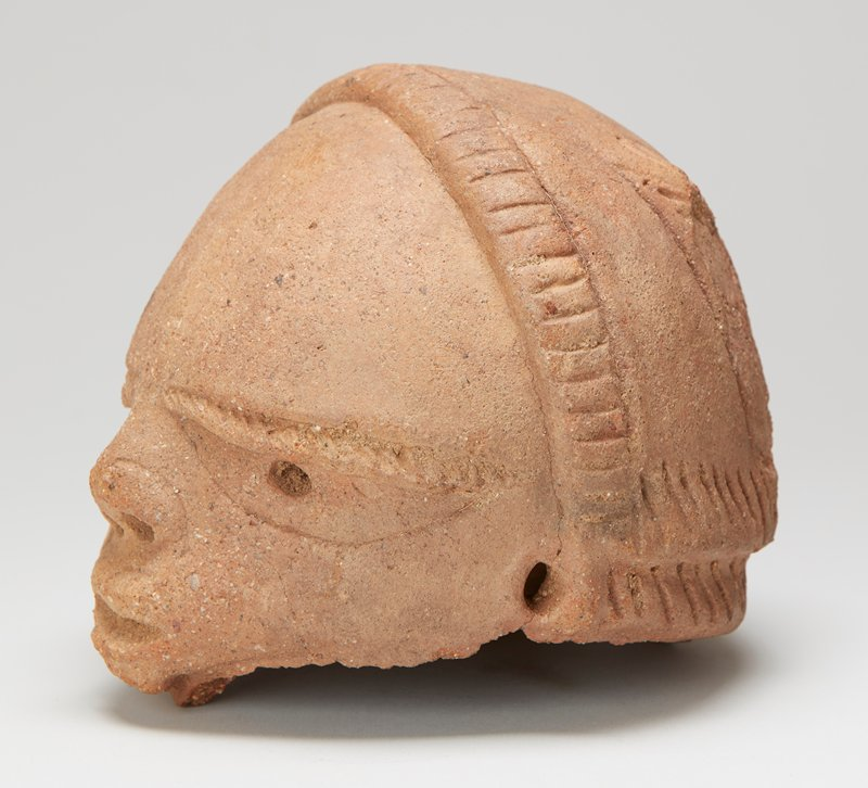 top part of head to chin; extremely large eyes with incised pupils; slightly protruding lips; flat ears with incised canals; hairstyle with 2 earlike tufts on back of head (PL tuft missing)