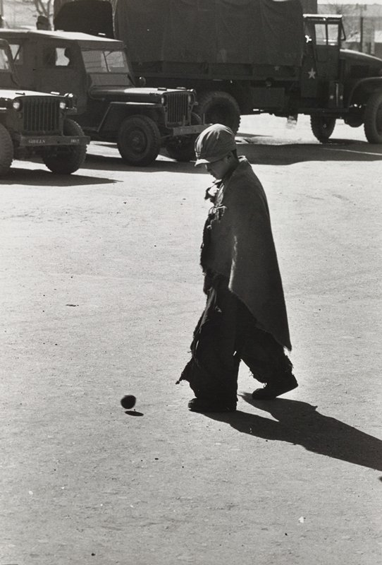 boy wearing a cap, torn pants and a fraying cloth wrapped around his shoulders kicking a small ball; military trucks and jeeps in background