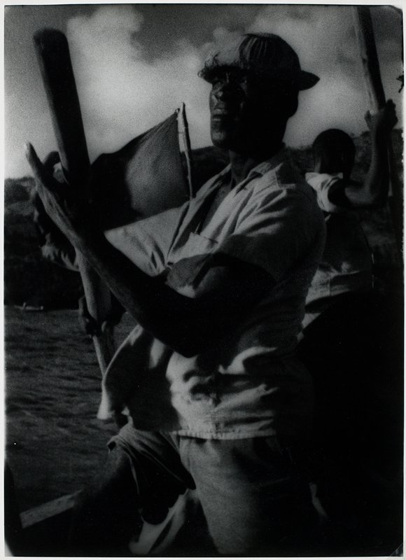 black man wearing a small cap, standing on a boat with a large pole at his PR side; another man in background