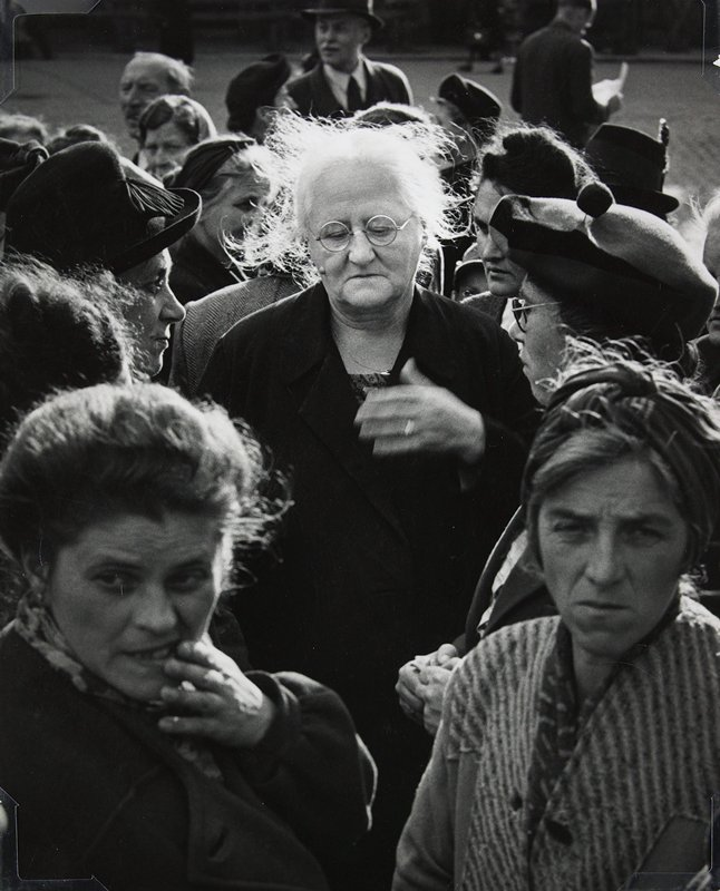 elderly woman with white disheveled hair, wearing glasses and looking down, at center; group of women clustered around her with men in background