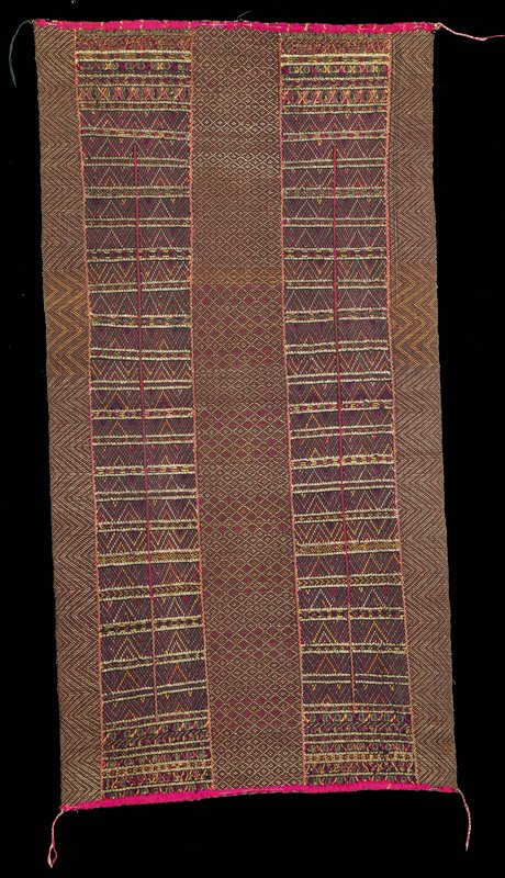 weave type (?) brown ground with large zig-zag patterning at outside edges and lozenge pattern at center; 2 vertical rectangular bands of patterning; worn pink border (wool?) at top and bottom; braided cords at 3 corners; string at 4th corner