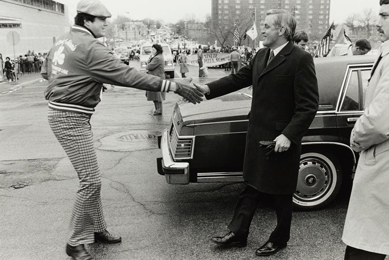 Man in checked pants and hat shaking hands with Walter Mondale