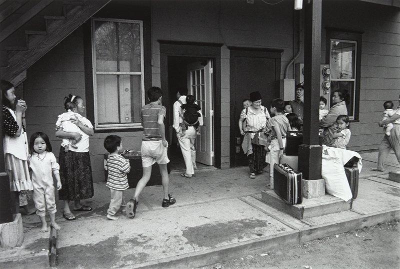 black and white photo of men, women, children, suitcases on sidewalk in front of open door