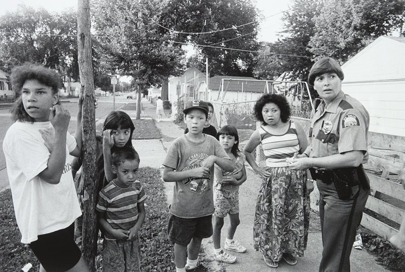 black and white photo of group of children and adult with St. Paul police officer on sidewalk