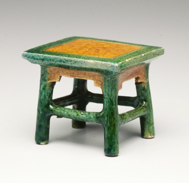 Tomb furniture; small, nearly square table with tan glazed top inside an incised square and tan glazed apron; green glazed tabletop edges and legs