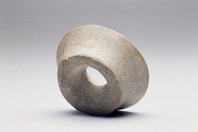 Round with hole in center; one smaller flat side flaring out on edges; grey stone with bluish flecks