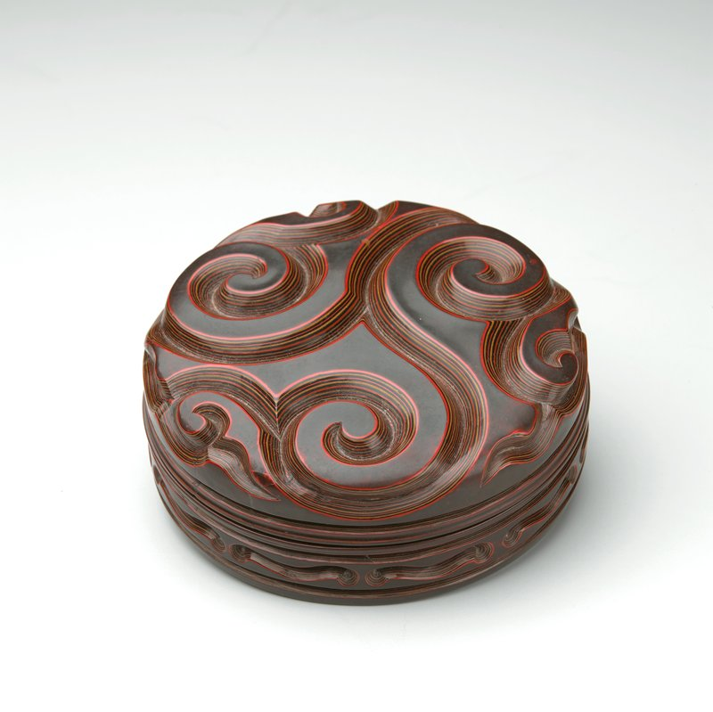 box carved with Guri design (scroll pattern divides lid into three sections); sides carved with curved horizontal lines; thick carving reveals several layers of lacquer