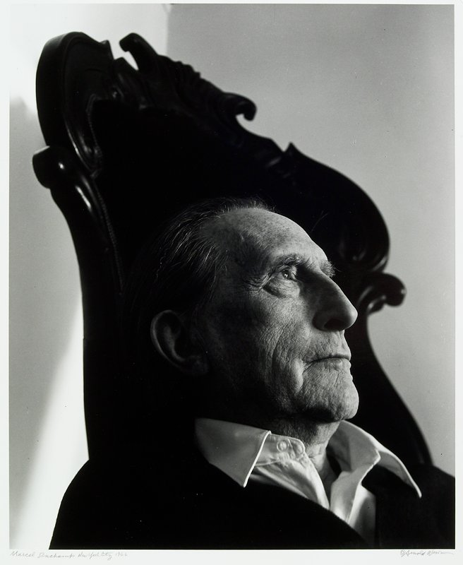 profile of man's head; man is wearing a shirt with white collar and sitting in a high-back chair