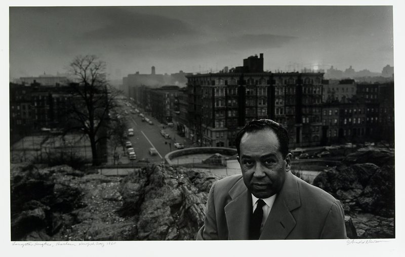 man wearing suit and tie LRQ; rocky outcrop immediately behind man; city neighborhood in background