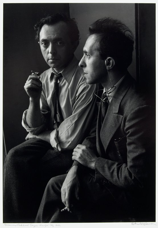 two men smoking; one looking at camera, the other in profile