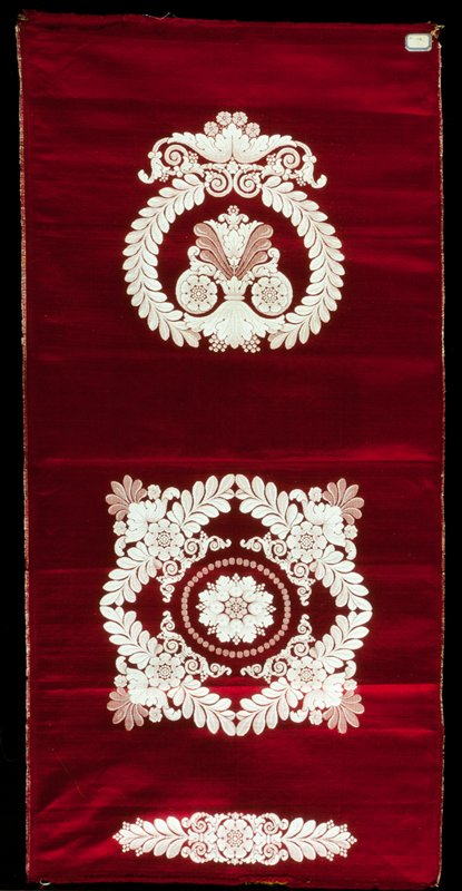 upholstery material designed for chair seat and back, red satin with white floral designs.