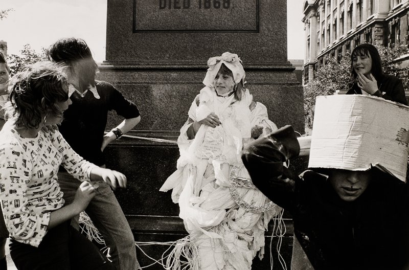 bride-to-be wrapped in white paper from head to toe; flanked by several friends looking on