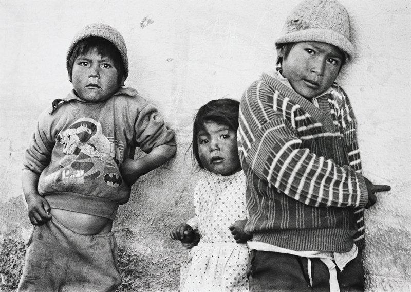 three children leaning against a wall; boy on the PR is wearing a Batman shirt