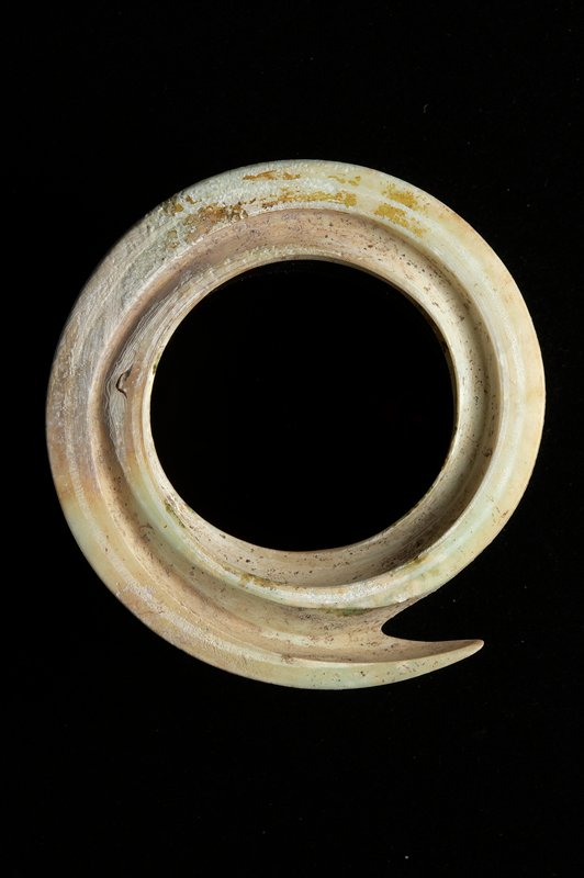 bracelet cut from a section of shell, forming a spiral with an open center; whitish with brownish and greenish areas
