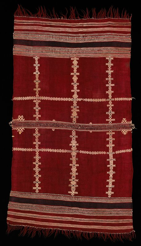 dark red with black and cream woven brocaded designs; stripes at each end and at center with rows of diamonds and half-diamonds to R and L of center; red fringe