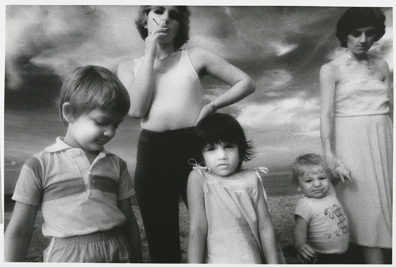 little boy, looking down, at L; little girl with dark hair at center, looking at camera; blonde woman wearing a tank top and smoking behind boy and girl; woman wearing dress at R holding a little boy's PL wrist, who wears a snoopy shirt