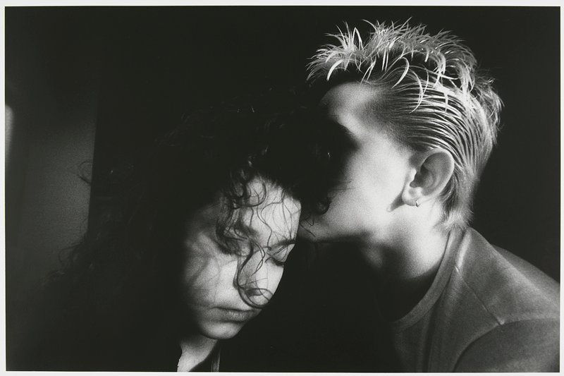 close-up of a young couple young woman on L with head bent toward PL, eyes closed, strands of hair in front of her face; young man on R in profile, face hidden in girl's hair, with blonde spiky hair and earring; matted