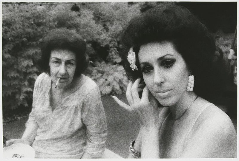 older woman wearing printed dress at L, smoking a cigarette; younger woman at R touching her PR ear, with long nails, wearing false eyelashes, large earrings, bracelet and a flower behind her PR ear