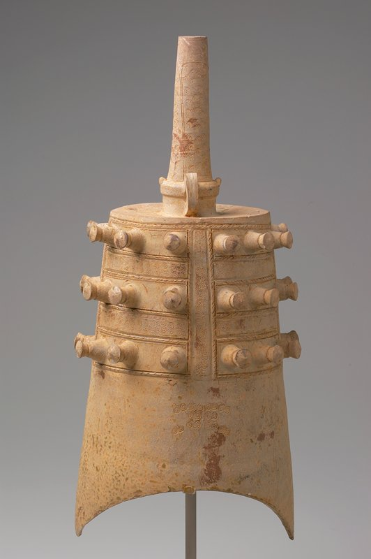 light tan glaze; tapering cylindrical shape with two arching cuts at bottom; 3 rows of protruding elements alternating with incised spiral; spirals on stem