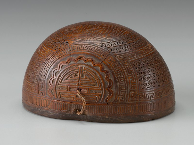 half of a gourd with flat portion of wood; gourd carved overall with geometric designs; radiating half-circle door on one side
