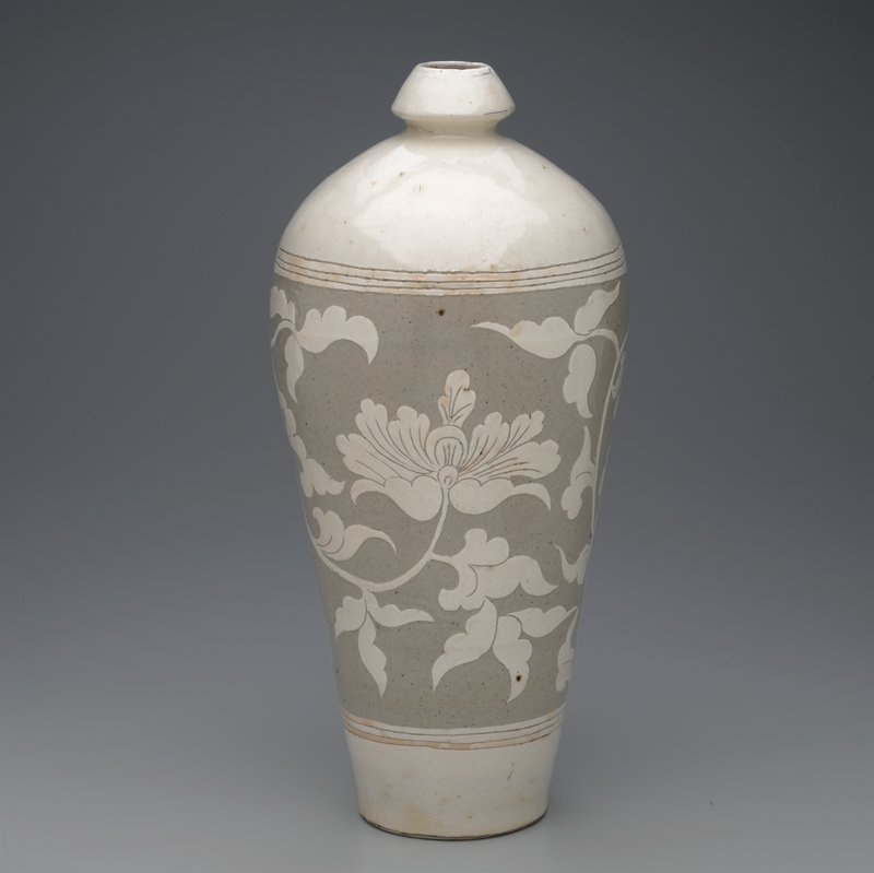 slender meiping shape with rounded shoulders and reel-top mouth; white slip over grey stoneware; central band of carved scrolling floral branches
