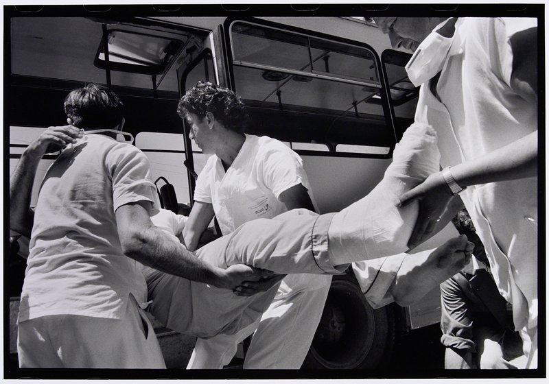 three men helping person with broken leg into a bus