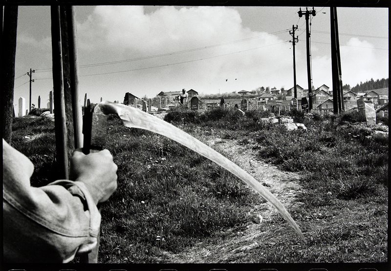 hand holding scythe with view of cemetery in background