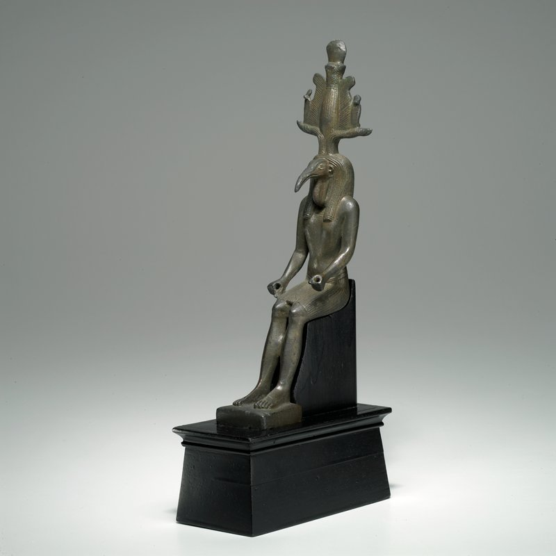 statuette, of ibis-headed god, seated, wears wig and atef crown. Thoth of Hermapolis was known as the scribe of the gods and the god of wisdom. The Ibis was sacred to him.