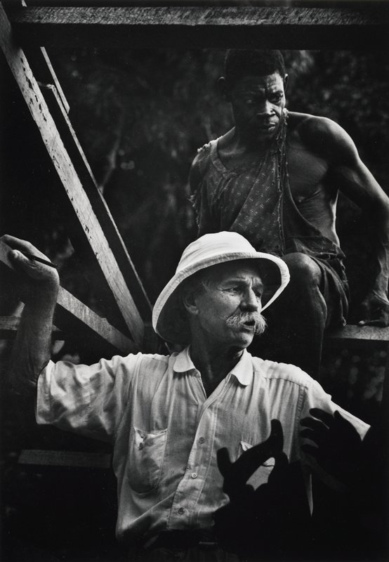 Dr. Schweitzer in foreground; black man seated on ledge above and behind; wood beams at top and left side
