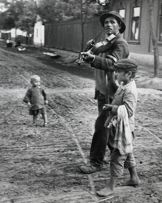 walking man playing a violin, wearing a hat, with a cane over his proper left arm; little boy wearing a cap walks next to man; toddler at left