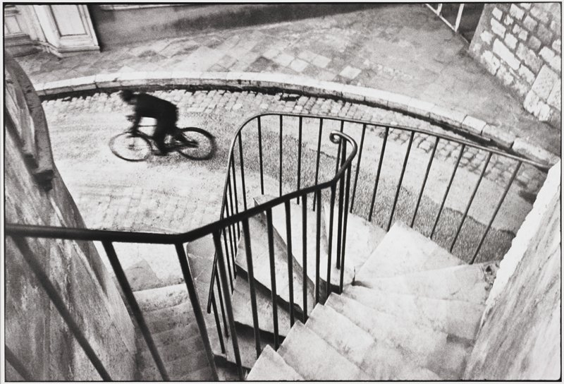man on a bicycle viewed from top of stairway; see L2005.262.64 which is the same image in smaller size
