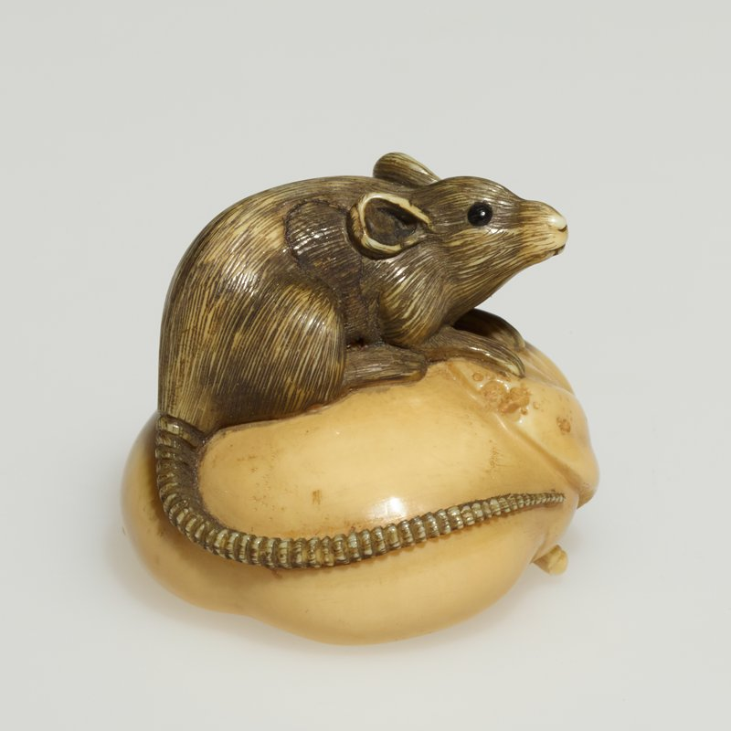 brown rat sitting on tan pillow shape with a leaf under its feet; branch & flower & two holes on bottom; other J #82