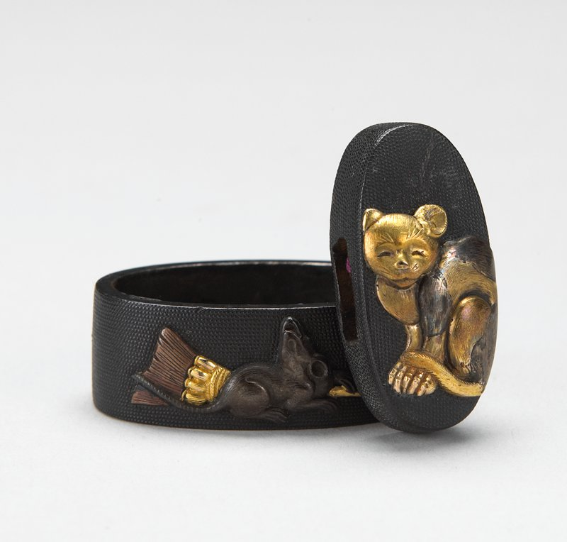 set of Fuchi-Kashira of a cat and rats; .1 decorated with one maise sitting on a gold-colored broom on front, another mouse on back; oval opening on top, semi-rectangular opening on bottom; .2 decorated with gold-colored cat; rectangular openings on 2 sides, oval opening on back; both in one wood box w/ purple lining