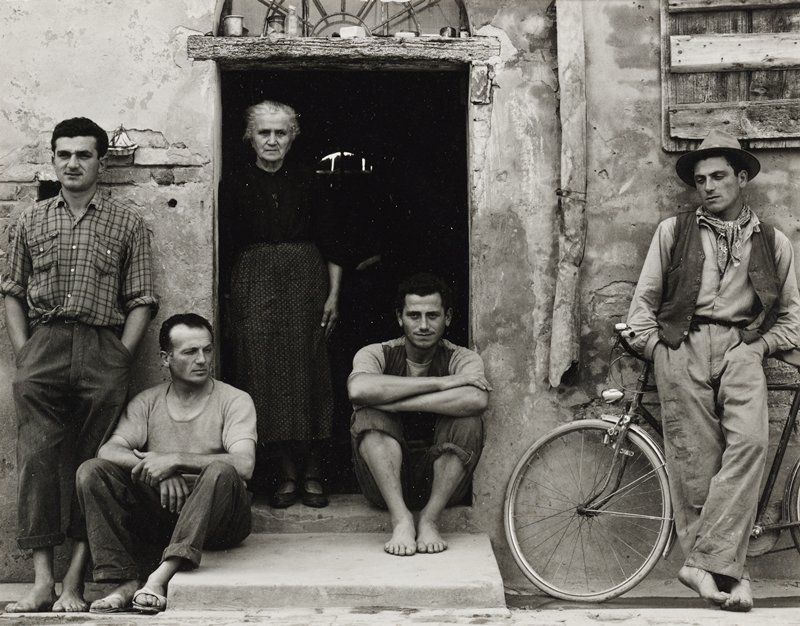 four men, one woman, standing in doorway, leaning on walls, seated of doorstep; man at right leans on bicycle