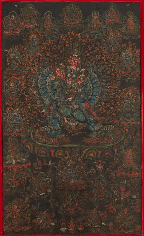 Rare black-ground thanka features the ferocious protective deity Vajrabhairava locked in cosmic embrace with his sakti, or female counterpart; he tramples birds, animals, demons and Hindu deities underfoot; his thirty-two secondary hands radiate around him, holding attributes; he wears garlands of severed human heads, skulls, and a five-skull tiara; central figures encircled by manifestations of the guardian Mahakala.
