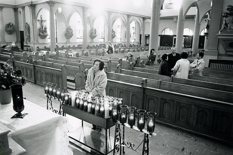 black and white photo of woman standing in front of candles inside church