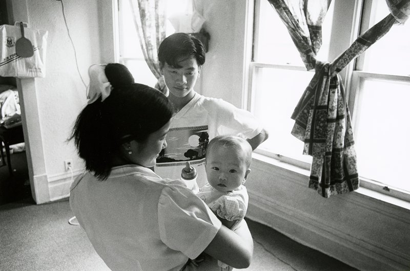 black and white photo of couple in front of windows; young woman holding baby