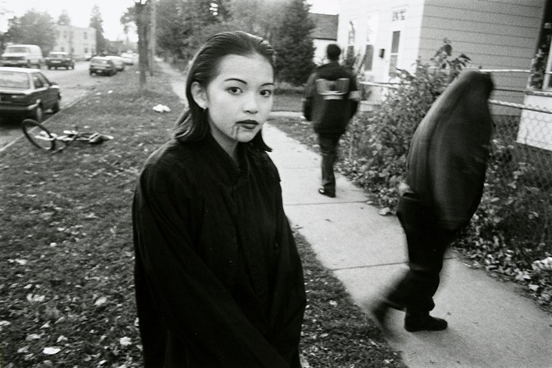black and white photo of girl with hair slicked back and two dark lines on chin