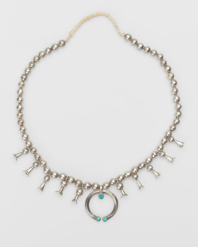 Single strand of silver beads; 10 squash blossoms of different styles and sizes, simple cast carinated naja set with three round flat turquoises in serrated bezels; wound string.(Beads dented, one hole) J.#398, Cat.#370.