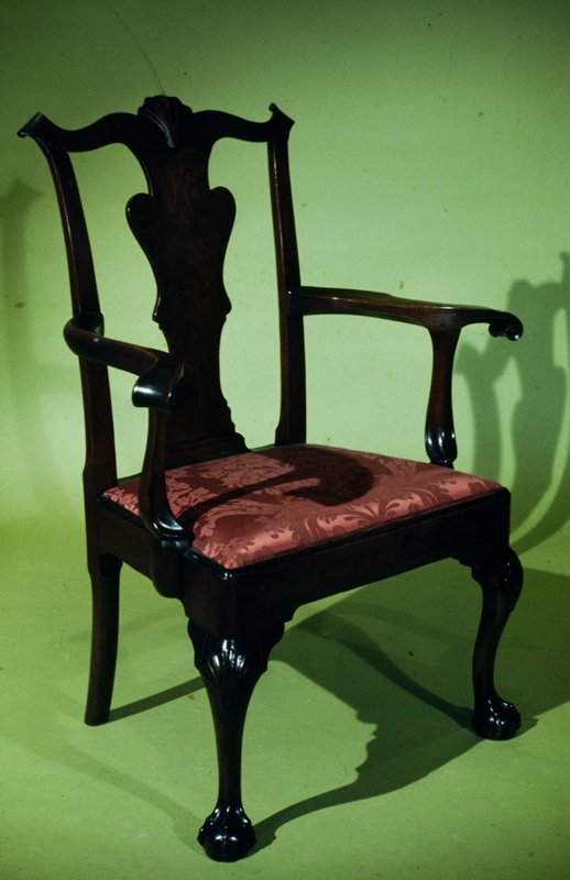 arm chair, Chippendale style; solid urn-shaped splat supports boldly curved crest rail with carved shell ornament in center; arms curve outward and terminate in broad volutes; shells ornament the knees of the cabriole legs that terminate in claw and ball feet; slip seat upholstered in crimson damask; Philadelphia type, possibly made by Savery