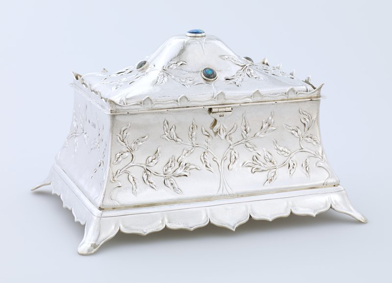 rectangular tapered box skirted by pointed lobes; body decorated by leaf plants growing from lower corners and center points at long sides; 5 semi-precious stones mounted at top; light wood box liner; crown of points around perimeter of hinged cover
