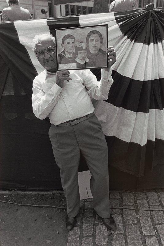 man displaying framed family portrait