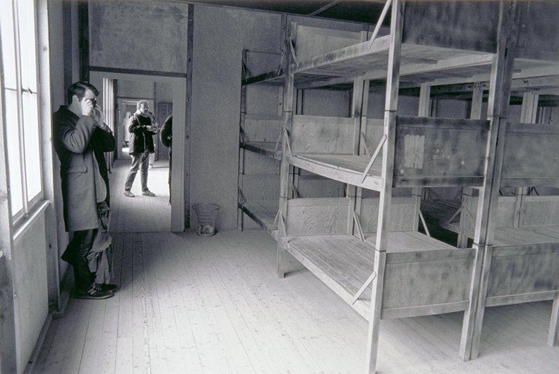 man in doorway looking at three tiered bunks