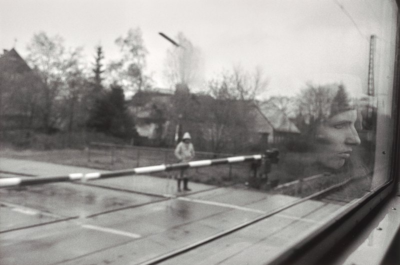 train window, reflection of woman's profile and gate