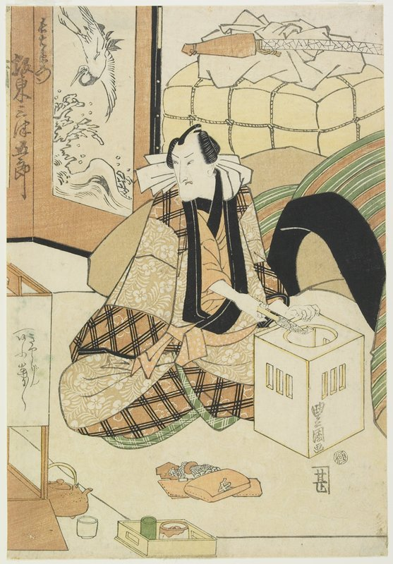 the actor lights his pipe in a brazier; his tobacco pouch, pipe case, ojime and netsuke set lie on the floor in front of him