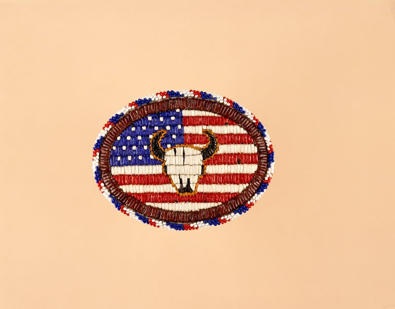 Oval buckle with beading around outer edge in red, white and blue beads. Brown band of quillwork separates beaded area from center quillwork. Center is an American flag with a cow skull on top of it.