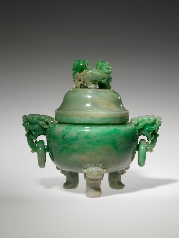 the globular body left entirely plain, with high polish showing the bright green stone with icy mottling and some darker green flecks and traces of white, with a pair of monster mask and loose ring handles, the tripod supports also issuing from monster masks and the domed cover with two fu lions forming the finial; carved of light green stone with white and green markings. Former Classification: Jade