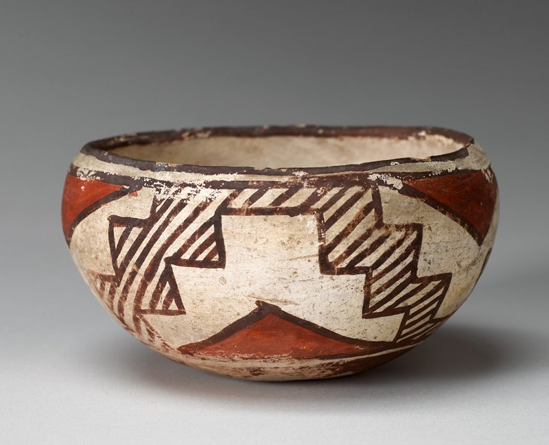 Round bowl with white base color, brown around rim, with brown and red design throughout; red triangles with brown stair step pattern. On bottom is eight pointed star