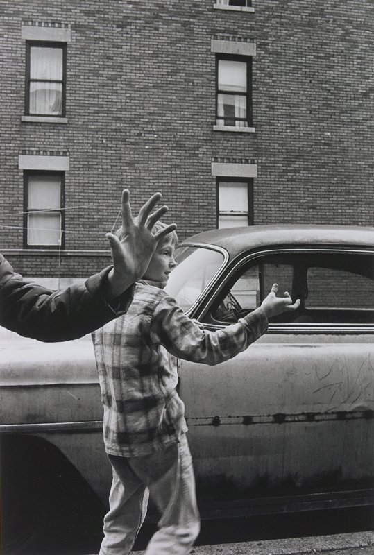 boy wearing a plaid shirt, standing in front of a car, stretching a rubber band (or string?) with his PR hand; arm with hand in front of boy's head also stretching rubber band (or string)