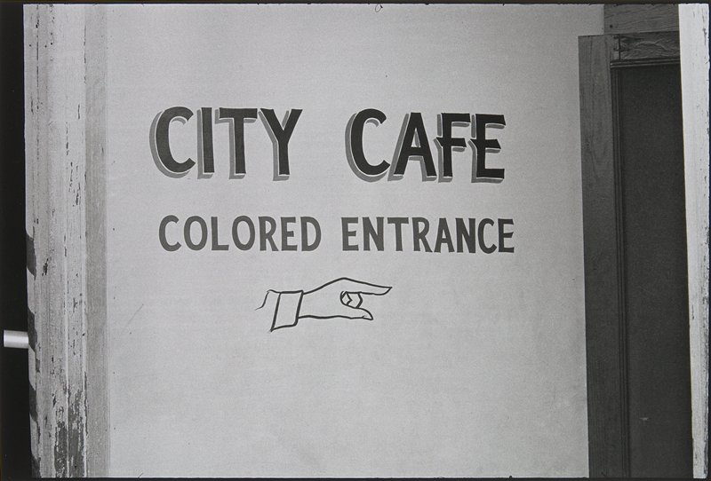 "sign reading ""CITY CAFE/COLORED ENTRANCE"" with a pointing finger painted below"